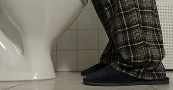 Man using toilet during the night